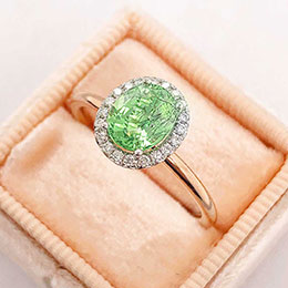 ring with diamonds and green gemstone